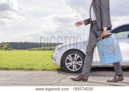 Low section of young businessman with gas can walking by broken down car at countryside