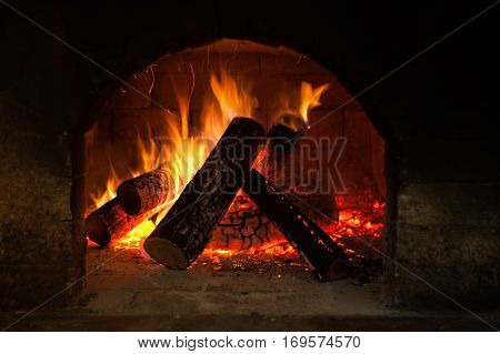 Burning fireplace, classic style interior detail. Warm cosy home, glowing flame closeup, atmosphere of comfort and relaxation