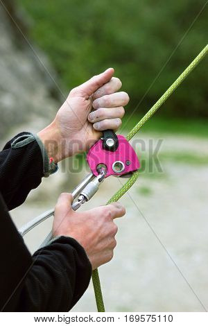 Insurance climber using ropes and belay device in action.
