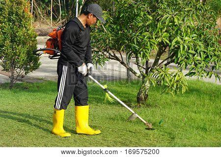 Labuan,Malaysia-Feb 5,2017:The worker of a garden cuts off a grass in Labuan,Malaysia on 5th Feb 2017.