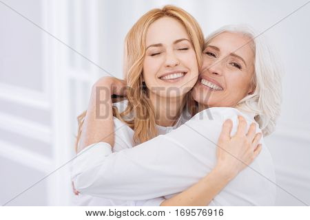 Parents love. Positive smiling aged woman expressing love and embracing with her daughter while resting at home together