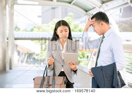 Stressed businessman and frustrated businesswoman in difficult situation. Young Asian secretary holding digital tablet with worried face. Manager suffering from headache.