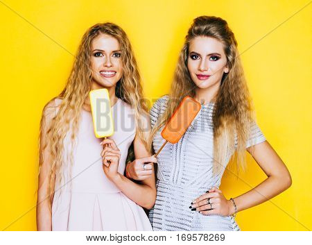 Two best friends having ice cream together indoor on yellow background. Close up of young women eating ice cream and having fun. Eskimo pie.