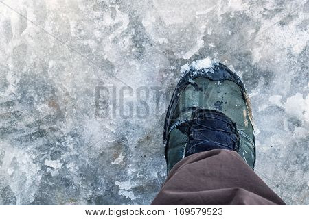First person view of hiking boot in the snow and slush