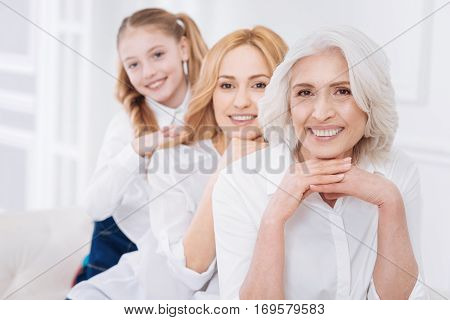 So nice. Delighted positive three generations of the femily smiling and sitting o the couch while having fun at home