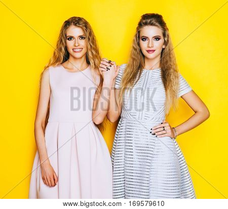 Friendship forever. Two stunning blonde girl in beautiful dresses are friends and they raised their hands. Indoor. On yellow background.