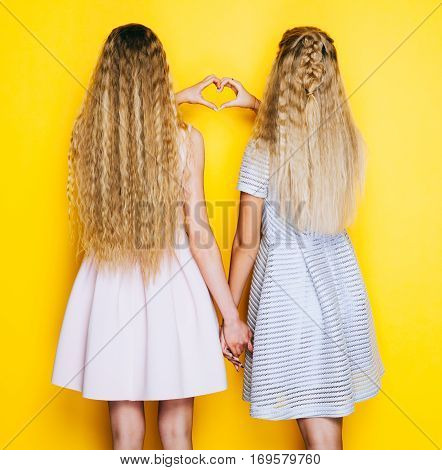 Love and friendship forever. Two girls girlfriends standing back and show making heart sign. Indoor. On yellow backgrownd.