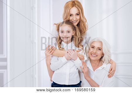 Family life. cheerufl content loving woman embracing her little daughter and snior mother while resting together at home and spending time with pleasure