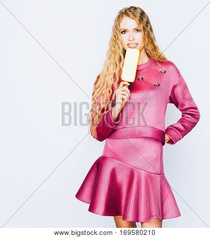 Beautiful young blond woman in fashionable purple dress eating popsicle. White background, indoor.