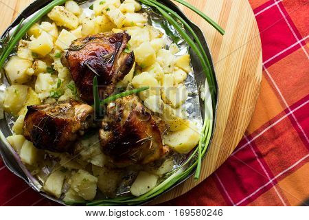 Appetizing baked potato in aluminum round dish with fried chicken and green onion and pickled cucumbers and garlic