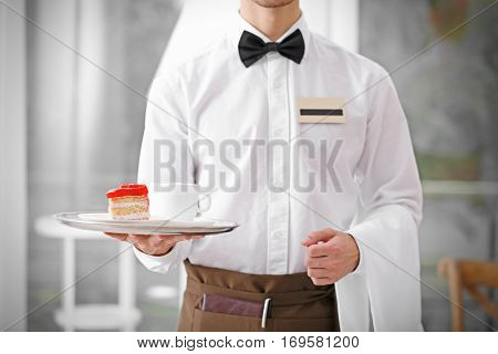 Waiter in white shirt bringing the ordered dessert and cup of coffee in a cafe