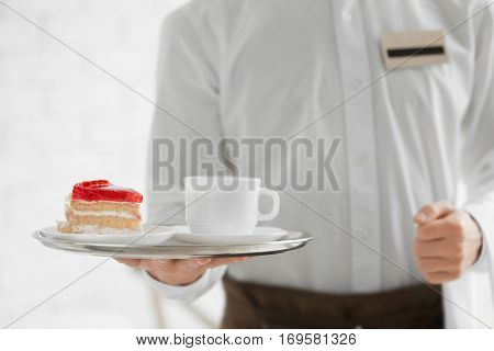 Waiter in white shirt bringing the ordered dessert and cup of coffee in a cafe, close up