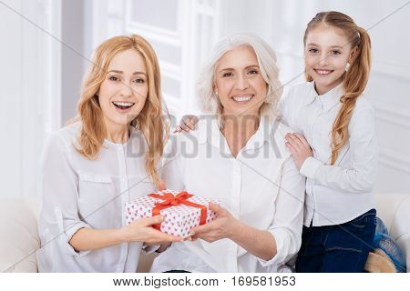 Thats a surprise. Cheerful delighted smiling three generations of the family sitting on the couch and holdign present while expressing positivity