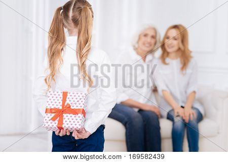 Ready for surprise. Pleasant little girl holding present behind her back and going to congratulate her mother who is sitting on the couch
