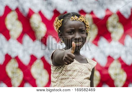 Young african girl with traditional accessories in hair showing thumbs up sign and looking at camera