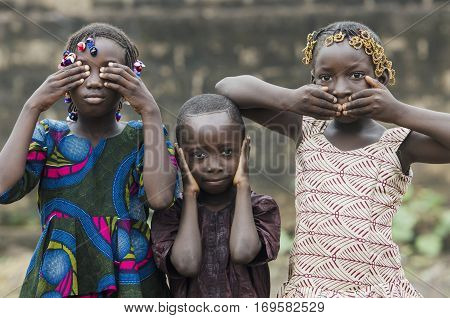 Young african girls and boy posing as famous three wise monkeys