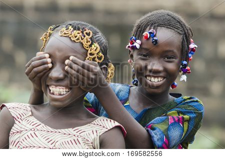 Two young african girls with traditional accessories in hair having fun in front of camera playing peekaboo