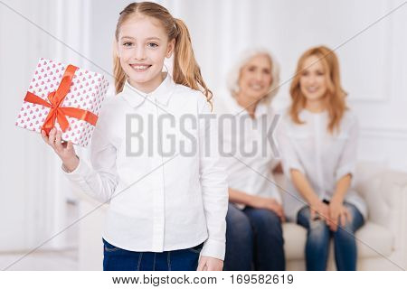 Nice surprise. Cheerful pleasant little girl holding present and smiling whileher mother and grandmother sitting in the background