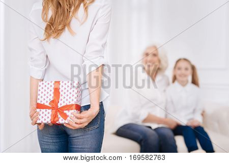 Ready for surprises Cheerful delighted woman holding present behind her back and going to congratulate while her daughter and mother sitting on the couch