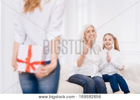 Full of gladness. Cheerful delighted woman and her little smilign granddaughter sitting on the couch while waiting for surprise.