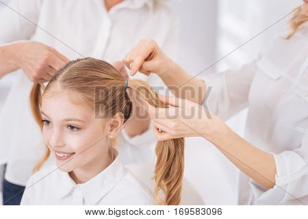 Like in hair salon. Cheerful delighted little girl expressing gladness while her loving pleasant mother makign ponytails for her