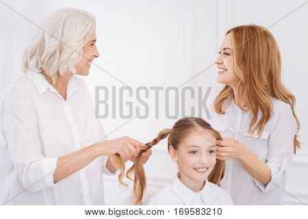Involved in process. Cheerful delighted smiling girl resting at home while her moter and loving grandmoter putting her hair in a plait