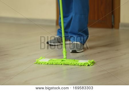 Close up view of man moping floor