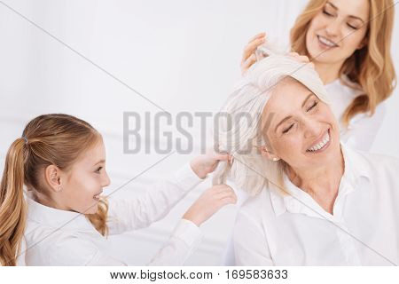 Rise your mood. Cheerufl content smiling aged woman sitting on the couch while her daughter and granddaughter playing with her hair while resting at home