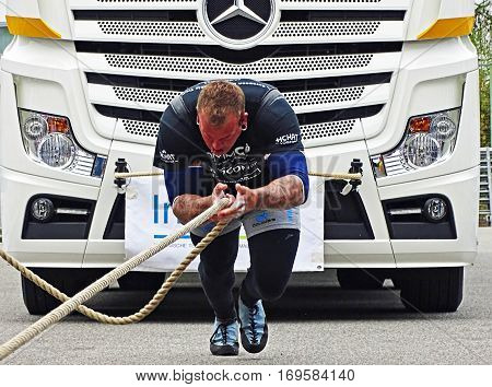 Chemnitz, Germany - October 4, 2015: A strong man pulls a 15 ton heavy truck with a rope in the final of FIROCON Truck Pull European Championships.