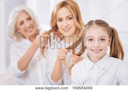 So bright and happy. Cheerful smiling girl resting with her mother and grandmother while making hairstyle for each other