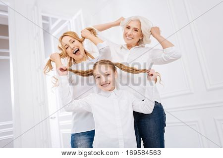 Playful mood. Cheeful happy little girl and her mother and grandmother smiling and expresssing joy while resting together