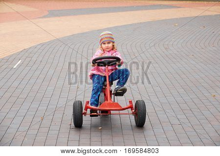 Little Girl Having Fun Driving A Pedal Car In Day.
