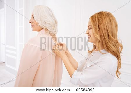 Help me. Positive attractive adult woman smiling and helping her mother to wear dress while buttoning up