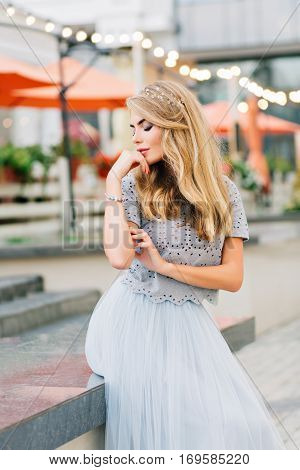 Pretty blonde girl in blue tulle skirt sitting on terrace background. She dreaming with closed eyes