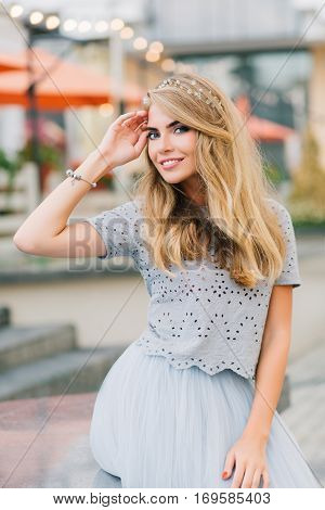 Portrait beautiful girl with long blonde hair in blue tulle skirt sitting on terrace background. She keeps hand on head and smiling to camera