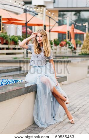 Attractive girl with long blonde hair in blue long tulle skirt sitting on terrace background. She keeps hand on head and looking to camera