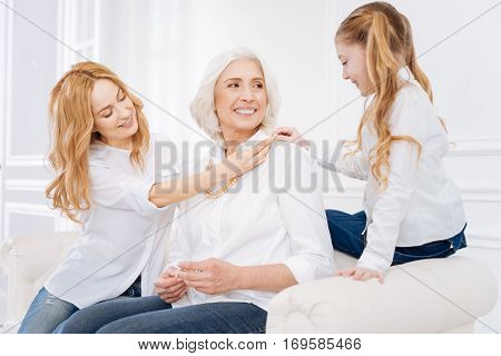 Womans world. Cheerful aged woman smiling and resting with her daughter and grranddaughter while sitting on the couch