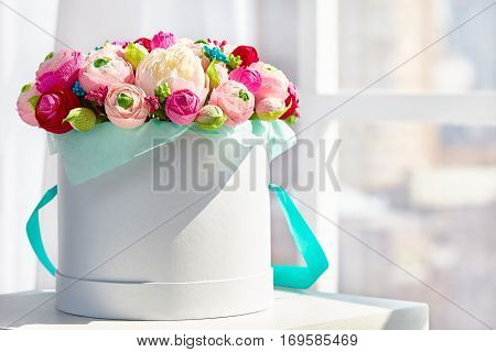 Colorful beautiful bouquets of pink, yellow and red flowers in the round box.