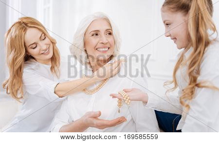 So pretty. Cheerful delighted aged woman wearing accessories while resting with her daughter and granddaughter at home