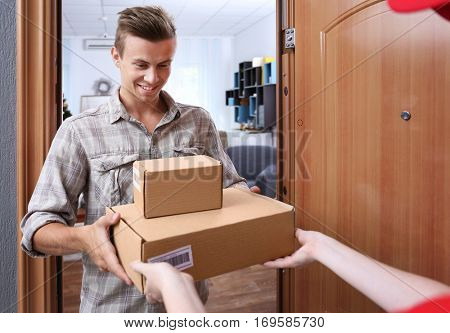 Young man receiving package from courier