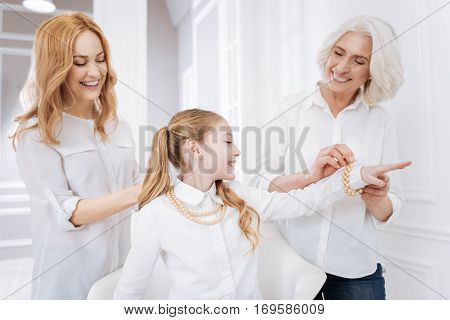 Prettify your life. Cheerul woman and her mother helping to wear accessories for little girl while resting at home