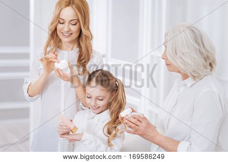 Beauty treatment. Cheerful female family members using beauty cream and resting together while expressing joy