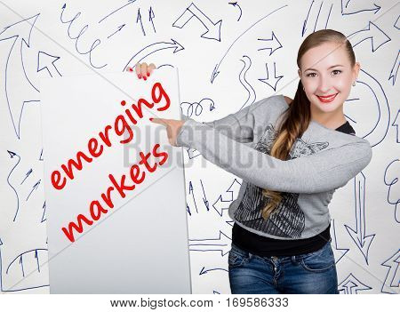 Young woman holding whiteboard with writing word: emerging markets. Technology, internet, business and marketing