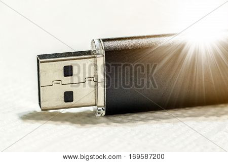 Black usb flash drive isolated on white background with sun beams soft light