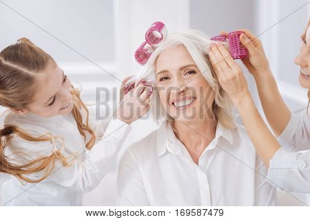Home hair salon. Positive contetn aged woman expressing positivity while her granddaughter and daughter helping her to curl hair