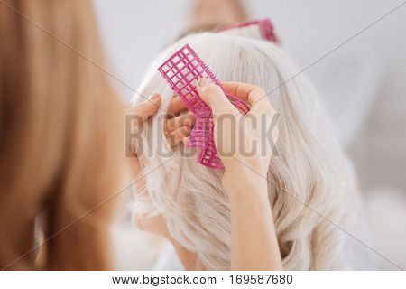 Day of beauty. Pleasant woman using hair curlers while making hairstyle for her aged mother