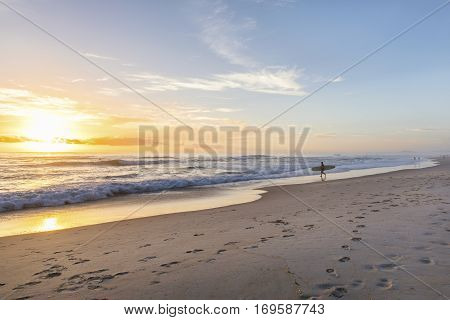 Surfer walking into the ocean at sunrise, on Gold Coast beach.