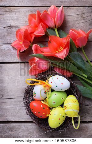 Easter composition. Fresh tulips flowers decorative eggs in nest on vintage wooden background. Selective focus.
