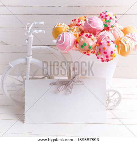 Empty tag and bright cake pops in decorative bicycle on white wooden background. Selective focus. Place for text. Square image.