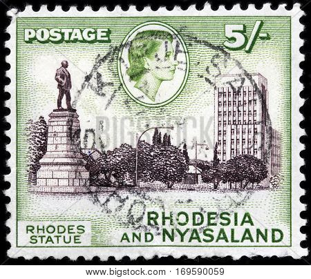 LUGA RUSSIA - SEPTEMBER 18 2015: A stamp printed by RHODESIA AND NYASALAND shows image portrait of Queen Elizabeth II against view of Cecil Rhodes Statue circa 1959